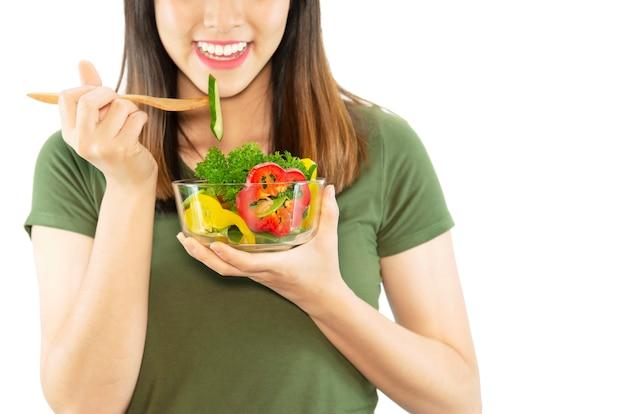 幸せな女性は野菜サラダを食べることを楽しむ 無料写真