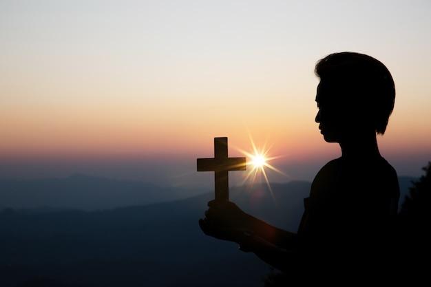 太陽の上の精神的な祈りの手がぼやけて美しい夕日と輝き 無料写真