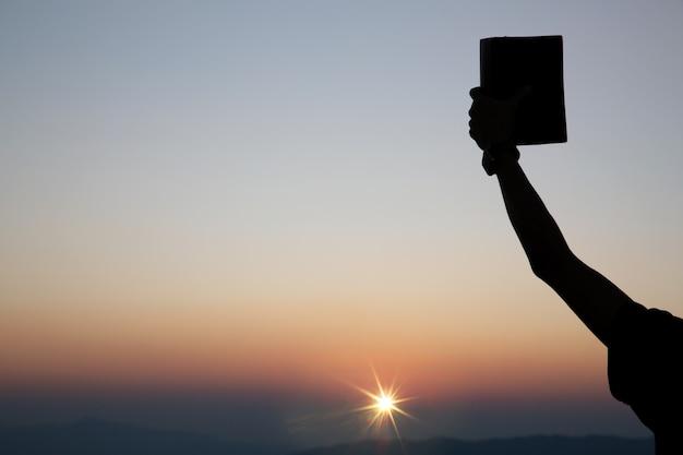 聖書を保持している霊的な祈りの手 無料写真
