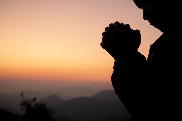 美しい空を背景に祈っている女の子のシルエット。 無料写真