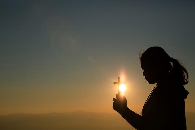 Девочка-подросток держит крест с молитвой. мир, надежда, мечты концепции. Бесплатные Фотографии