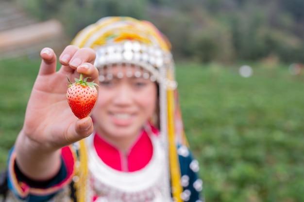 部族の女の子がイチゴを集めています 無料写真