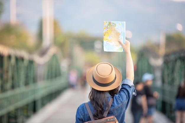 一方で女性観光客は幸せな旅行地図を持っています。 無料写真
