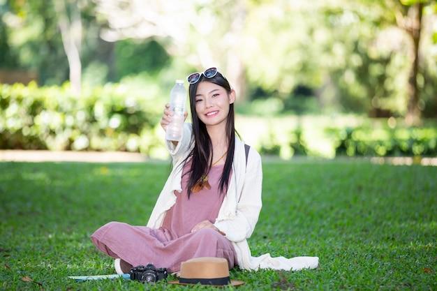 女性観光客は水を飲んでいます。 無料写真