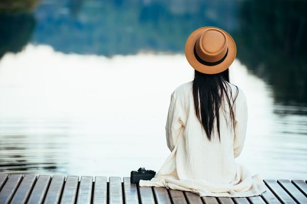 ウォーターフロントのいかだに座っている孤独な女性 無料写真