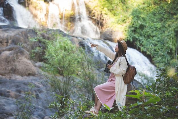 女性観光客は自然の上を歩いています。 無料写真