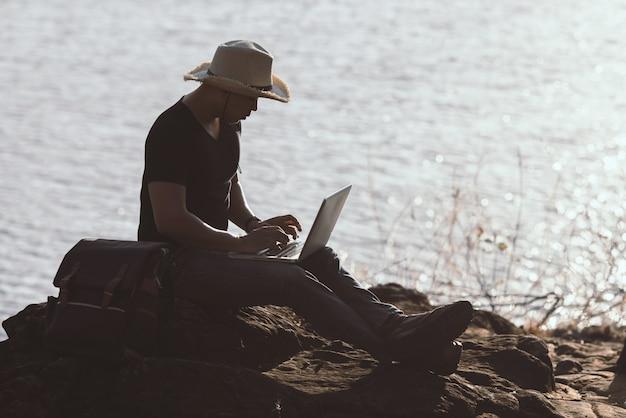 バックパッカーはラップトップを使用して山でリラックス 無料写真