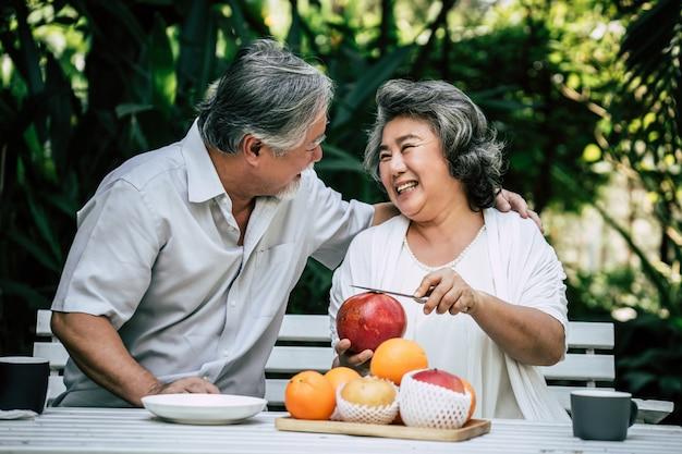年配のカップルが遊ぶことおよびフルーツを食べる 無料写真