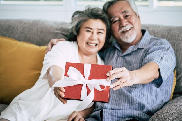 年配のカップルリビングルームでのサプライズとギフトボックス 無料写真