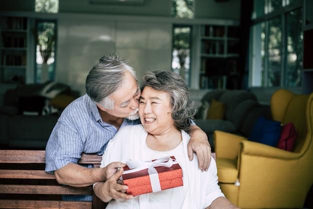彼の妻にギフト用の箱を与える驚きをする笑顔のシニア夫 無料写真