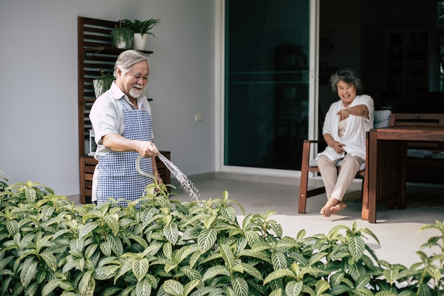 Пожилая пара поливает цветок в домашнем саду Бесплатные Фотографии
