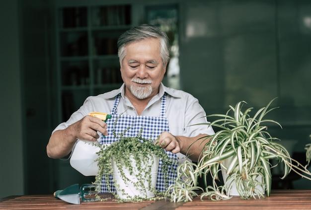 年配の男性が家に木を植える 無料写真