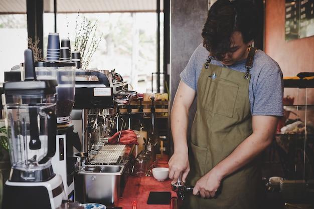 バリスタアジアがコーヒーショップでお客様のために一杯のコーヒーを準備しています。 無料写真
