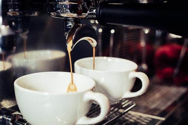 バリスタはカフェでコーヒーマシンを使用しています。 無料写真