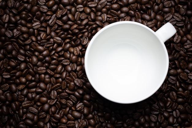 コーヒー豆とコーヒーカップ。 無料写真