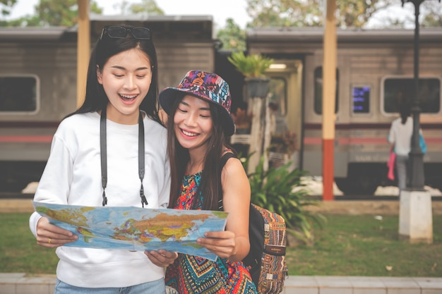 Две женщины держат карту в ожидании поезда. концепция туризма Бесплатные Фотографии