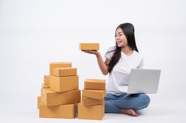 幸せな女パッケージ箱が手にあります。白背景オンラインショッピング事業者 無料写真