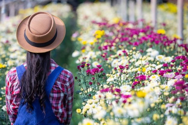 少女は庭の花を賞賛しています。 無料写真