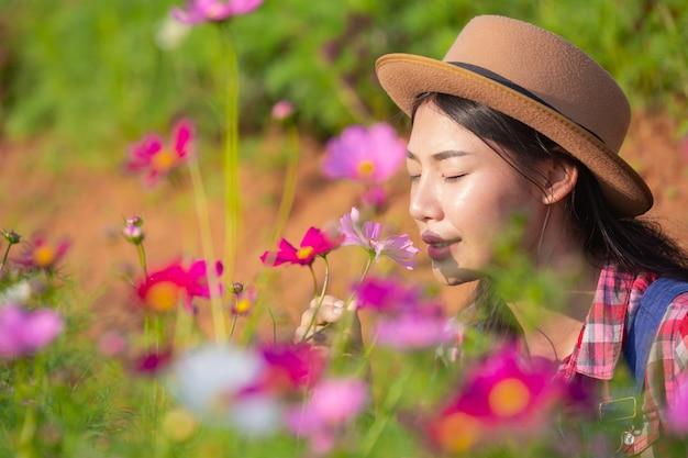 女性農家は花畑を賞賛しています。 無料写真