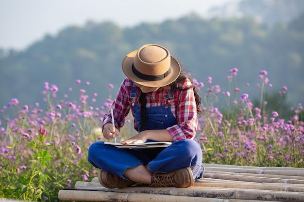 農家の女性は花畑でメモを取っています。 無料写真