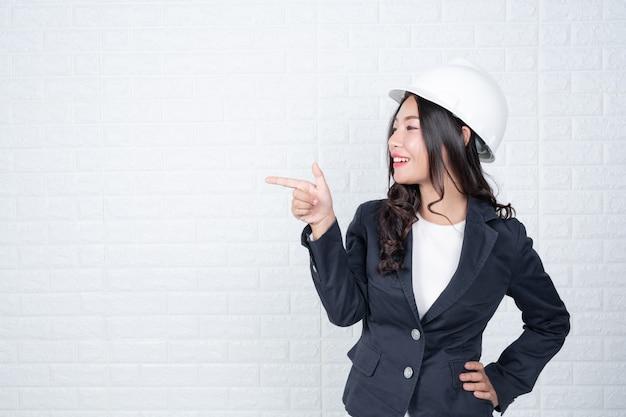 帽子をかぶって工学の女性、白いレンガの壁を分離した手話でジェスチャーをしました。 無料写真