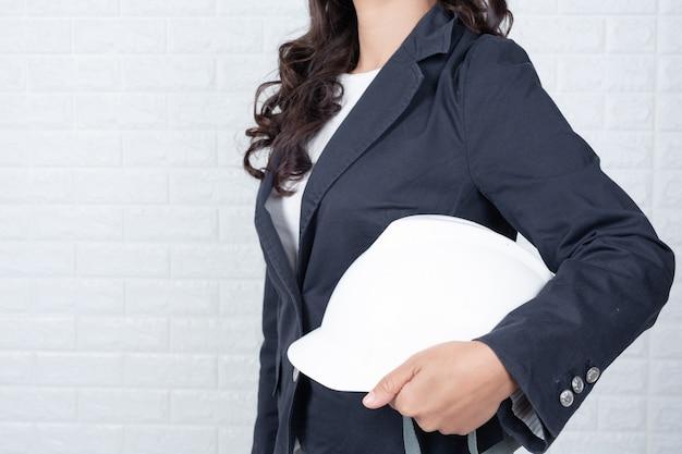 Инженерная женщина, держащая шляпу, отделяет белую кирпичную стену от жестов с помощью языка жестов. Бесплатные Фотографии