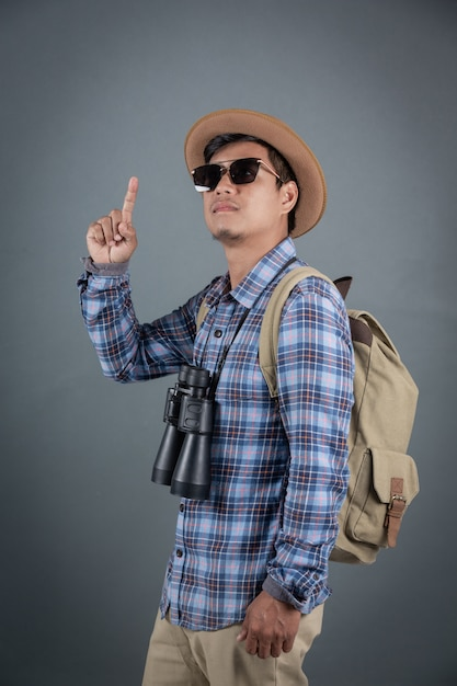 灰色の背景を保持している双眼鏡をバックパッキングの男性観光客。 無料写真