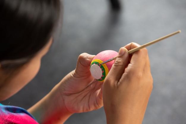 若者はイースターのために卵を準備するのを助けています。 無料写真