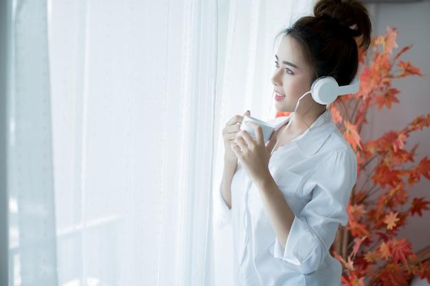 自宅で音楽を楽しんで明るい服装で美しい女性 無料写真