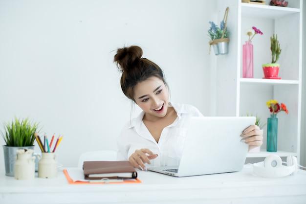 美しい若い女性は彼女の部屋で彼女のラップトップに取り組んでいます。 無料写真