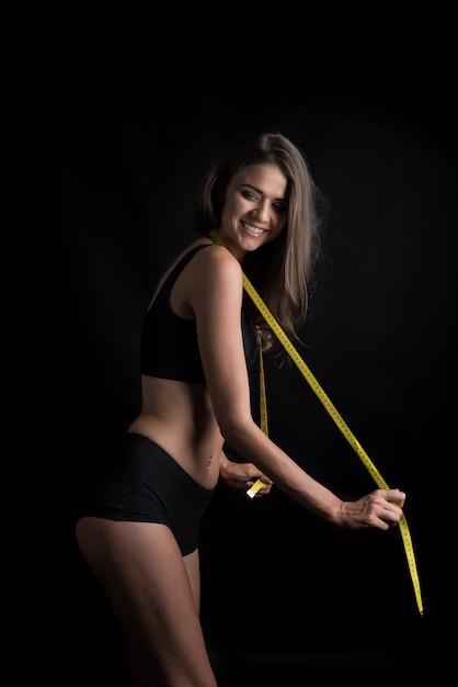 巻尺と彼女の体型のサイズを測定美しい若い女性の肖像画 無料写真