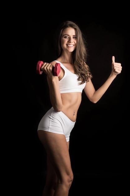 ダンベル運動をする若い美しい女性の肖像画 無料写真