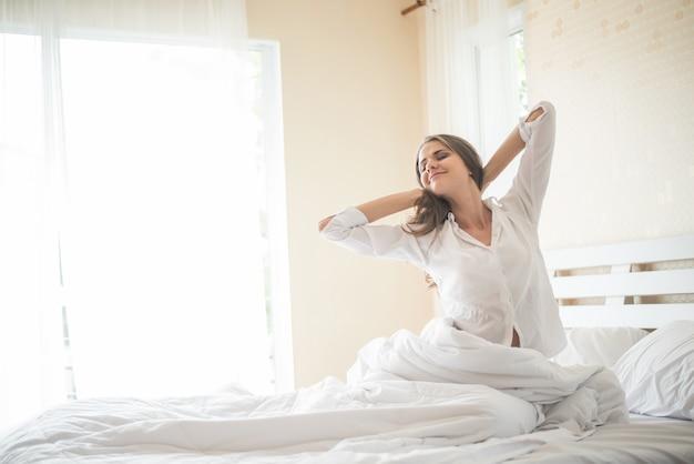 Ленивая молодая женщина сидит в спальне Бесплатные Фотографии