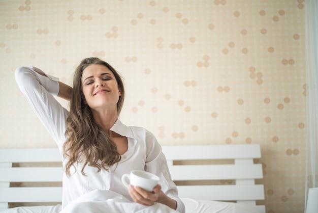 朝はコーヒーを飲みながら彼女の寝室で美しい女性 無料写真