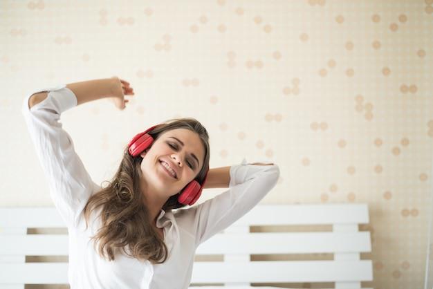 美しい女性が自宅のベッドに座って朝の音楽を聴く 無料写真