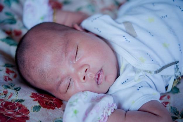 アジアの赤ちゃんがベッドで寝ています。 無料写真