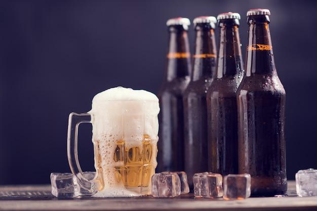 Стеклянные бутылки пива со стеклом и льдом на темном фоне Бесплатные Фотографии