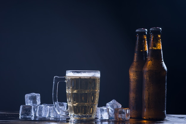 ガラスと氷と暗い背景にビールの入ったガラス瓶 無料写真