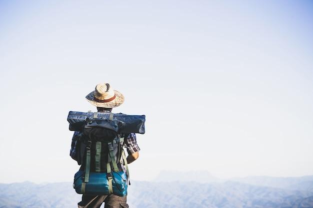 山頂からの観光客。太陽の光。男は太陽の光に対して大きなバックパックを着用します。 無料写真