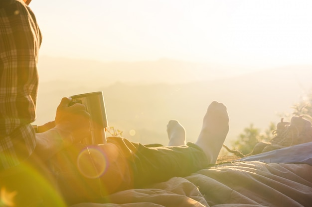 コーヒーカップを持ってテントの中で座っている若い男 無料写真