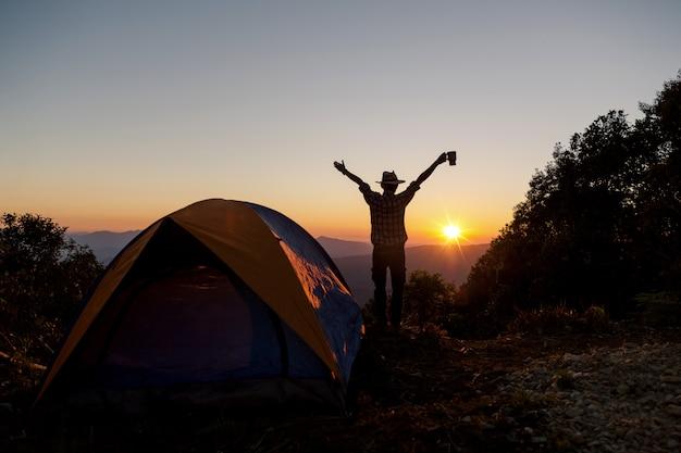 コーヒーカップを持って幸せな男のシルエットは山の周りのテントの近くに滞在します。 無料写真