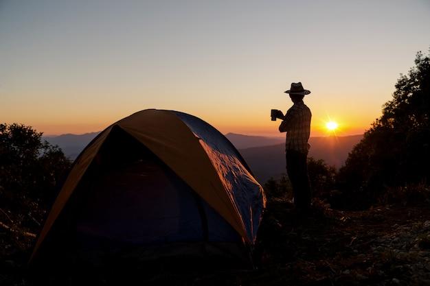 Силуэт счастливого человека с проведением чашки кофе возле палатки вокруг гор Бесплатные Фотографии