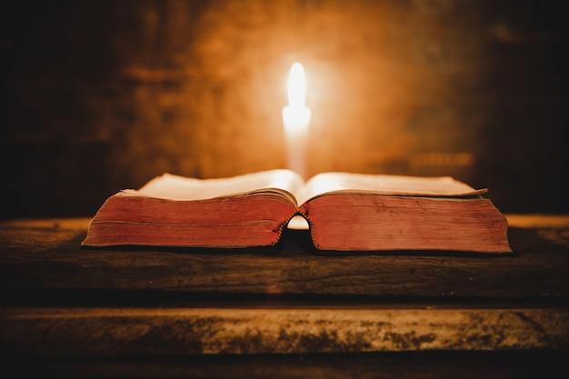 聖書を開き、古いオークの木製のテーブルの上のろうそく。 無料写真
