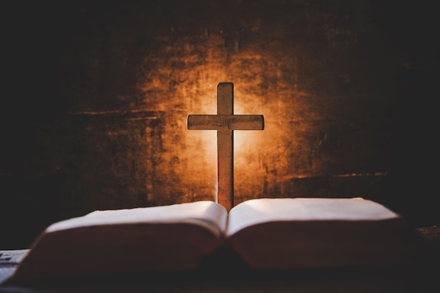 聖書と古いオークの木製のテーブルの上のろうそくを渡ります。 無料写真
