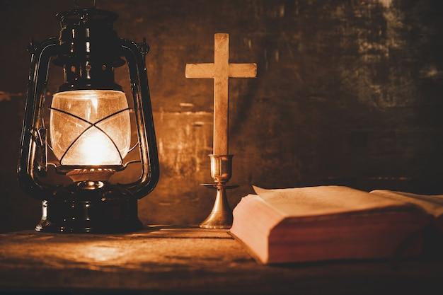 Крест с библией и свечи на старый деревянный стол из дуба. Бесплатные Фотографии