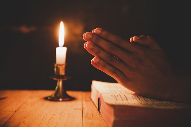 Человек молится на библии в свете свечи выборочный фокус Бесплатные Фотографии