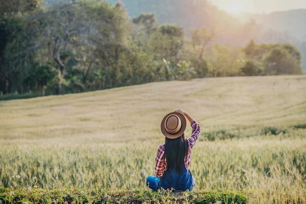 大麦畑の収穫シーズンを持つ女性農家 無料写真