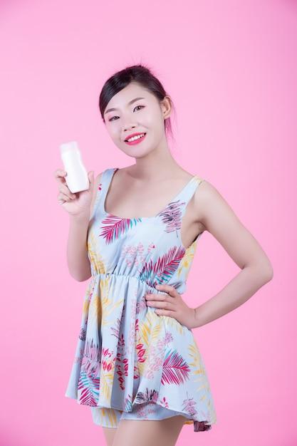 Красивая азиатская женщина держа бутылку продукта на розовой предпосылке. Бесплатные Фотографии