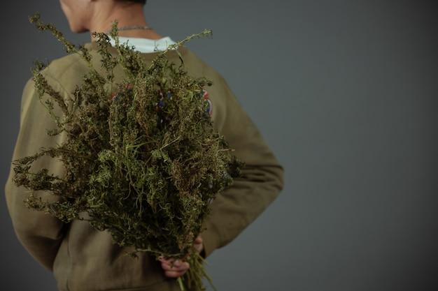 プランターは、灰色の背景に大麻の木を保持します。 無料写真