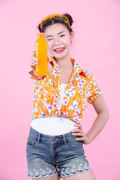 女の子はピンク色の背景にオレンジジュースの瓶を保持しています。 無料写真